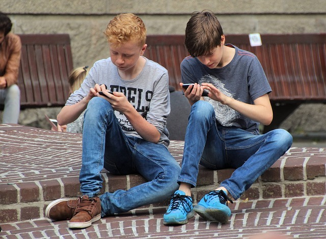 two boys on smartphones